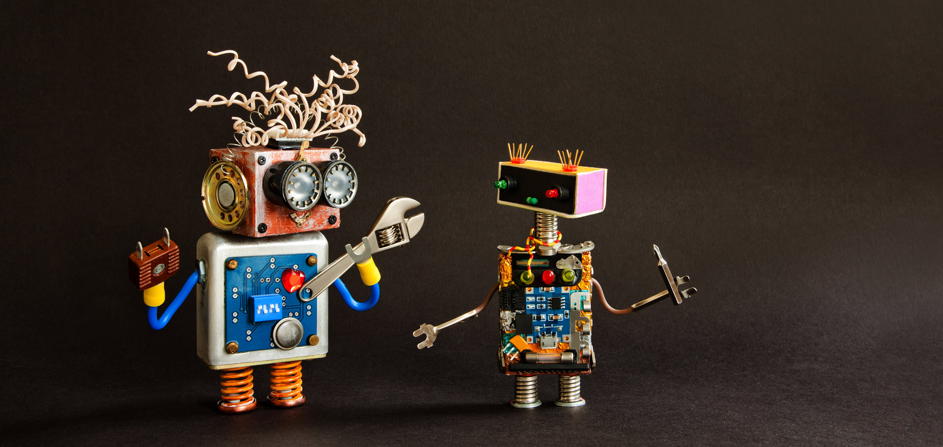 Two small robot friends crafted from electronic bits