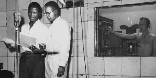 Photo of Sydney Poitier at microphone in recording studio