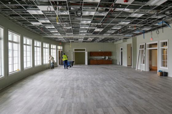 Unfinished large interior room with wood flooring